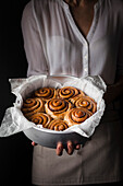 A person holding a baking pan of cinnamon rolls