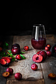 A glass of plum juice and fresh plums