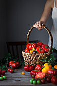 A person holding a basket of heirloom tomatoes