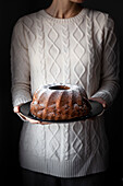 A person in a cozy sweater holding a bundt cake.