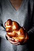 A person holding a loaf of brioche bread.