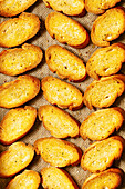 Slices of freshly baked crostini bread on baking parchment