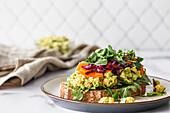 Fresh vegetarian sandwich with carrots, cabbage, pea shoots and chickpea salad on a plate