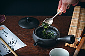 Japanese green tea – loose leaves being put into a teapot