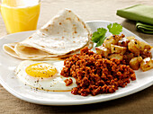 Mexican style Chorizo and fried egg breakfast with tortillas and hash browned potatoes