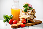 Toasted melted cheese pressed sandwiches with ham meat, cherry tomatoes and orange juice