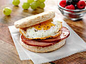 Canadian Bacon and fried egg breakfast sandwich on an English Muffin with fruits
