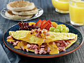 Ham and cheese omelette with fruits with English muffins and orange juice
