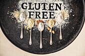 'Gluten free' Schriftzug in Mehl und Löffel mit verschiedenen glutenfreien Mehlsorten