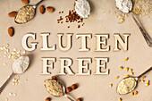 Metalllöffel mit verschiedenen glutenfreien Mehlsorten und 'Gluten free' Schriftzug