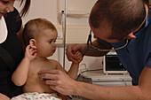 Paediatrician checks a baby's heart beat