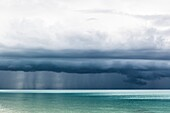 Storm clouds building up over tranquil tropical waters