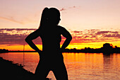 Silhouette of a woman at a riverbank at sunset