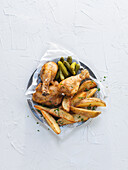 Roast chicken with potato wedges and cornichons