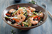 Dish with shrimps, rice, olives and zucchini