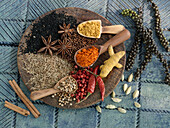 Various spices on small wooden scoops and a wooden board