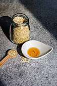 Healthy food concept with sesame seeds in glass jar and oil