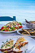 A table laid by the sea with Greek salad, octopus and fried sardines