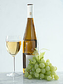 Glass and bottle of white wine with grapes