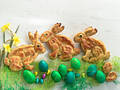 Easter bunnies made of puff pastry decorated with coloured Easter eggs, chocolate eggs, daffodils