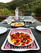 Grilled peaches with sun-dried tomatoes on a laid table outside