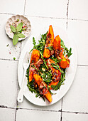 Pumpkin slices wrapped in bacon on rocket salad