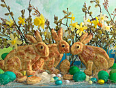 Easter bunnies made of puff pastry, coloured Easter eggs, chocolate eggs, daffodils and willow catkins