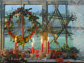A wreath, a star and candles in a window as Christmas decorations