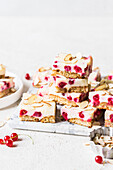 Sweetened condensed milk and degestive cookie slice with fresh redcurrants and almond flakes