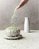 A hand pours green bamboo-infused rice into a decorative ceramic bowl