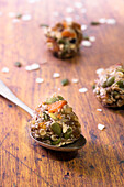 Healthy muesli cookie mixture rolled into balls with one on a spoon