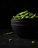 Black ceramic bowls filled with bright green edamame pods shot