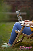Woman using laptop in garden lawn chair
