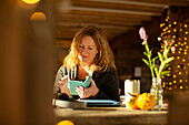 Businesswoman using smart phone at cafe table