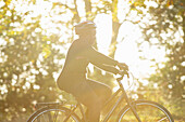 Woman in helmet riding bicycle in sunny autumn park
