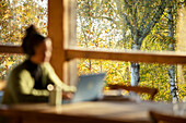 Woman working on laptop in cafe with autumn tree view