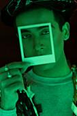 Man holding polaroid over face