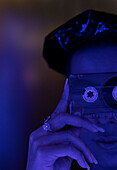 Young man holding cassette tape over face