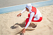 Female track and field athlete in hijab long jumping in sand
