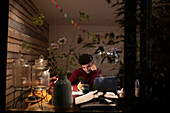 Young man with smart phone working from home at night