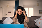 Smiling woman with headphones working from home on sofa