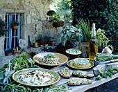 Verschiedene Gerichte mit Kräutern auf Tisch im Freien