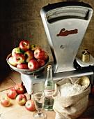 Stillleben mit Küchenwaage, Mehlsack und Äpfeln in einer Schale