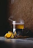 Dampfende Tasse Tee, Zitronenstücke und Zimtstangen