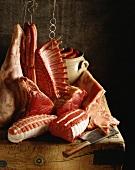 Verschiedene Stücke rohes rotes Fleisch und Würstchen, teilweise am Haken mit Hackbeil