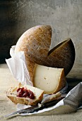 Angeschnittener Laib Ossau-iraty (Schnittkäse aus Frankreich) mit Brot und Konfitüre