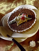 Chocolate tartlet decorated with a golden leaf