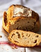 Ein angeschnittenes Brot auf Geschirrtuch