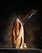 Ein spitzes Messer steckt in einem halben, aufrecht stehenden Baguette