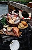 Stillleben aus verschiedenen Wurstwaren im Korb und auf Schneidebrett mit Brot auf einem Fischerboot